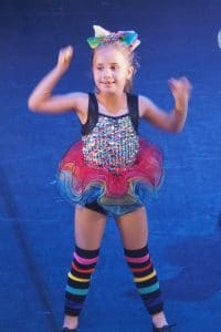 Young girl on stage in bright costume