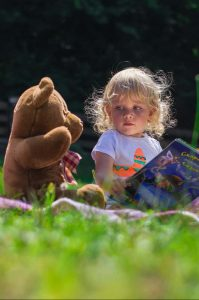 girl in field with toy bear and book