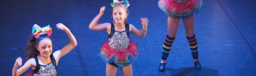 Three girls dance on stage bright costumes
