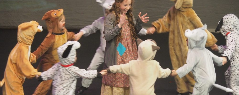 Small girl surrounded by children in fury costumes